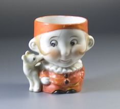 His dog loves him, despite his booboo. Egg Cup modelled as a boy wearing a pierot costume with a dog licking his face, made in occupied Japan between 1945 and 1952.