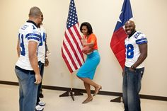 """Feb. 10, 2012    First lady Michelle Obama strikes the Heisman pose while greeting Dallas Cowboy football players, from left, Miles Austin, DeMarcus Ware and Felix Jones at the Kleberg Rylie Recreation Center in Dallas. The players joined the first lady and chefs from past seasons of """"Top Chef"""" for the """"Schools and Chefs Working Together"""" cooking competition to help promote the """"Let's Move!"""" initiative.  Chuck Kennedy / The White House"""