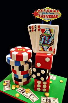 Vegas Cake! - I created this cake for a casino night.  Everything was edible except for the Vegas sign!  The sign had lights around it that flashed on and off.  I drew the queen of hearts playing card with edible food coloring markers.      The coins are fondant and the 100 dollar bills are edible images.  The poker chips were white almond cake with homemade raspberry filling and Swiss meringue buttercream. The dice were white almond cake with chocolate ganache. The playing cards were rice…