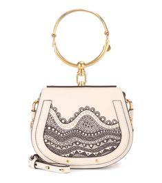 Chloé - Exclusive to mytheresa.com – Small Nile leather crossbody bag - Chloé's Small Nile crossbody bag has the signature charm the brand is known for. Crafted from smooth cream-hued leather and accented with golden hardware, this half-moon style features a doorknob-inspired top handle for a distinctive touch. This exclusive style comes in a swirling new-season print with a raised texture. Wear yours crossbody over a peasant top and loose trousers for bohemian flair. seen…