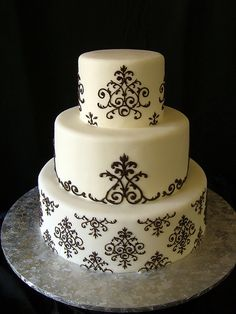 LOVE this cake with the damask pattern...hot pink gerber daisies added throughout would be my ideal cake! :)