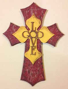 """Medium wooden, triple layer, wall cross. The back cross is painted with maroon acrylic and textured with beige and brown paint. The middle cross is painted in gold acrylic and distressed with brown paint. The piece is then topped with a laser cut piece of wood that spells out Love God and is stained brown. Dimensions are approximately 7.5"""" x 15"""". Each cross is handmade with love and truly one of a kind."""