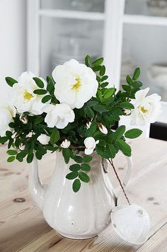 white roses in a white pitcher