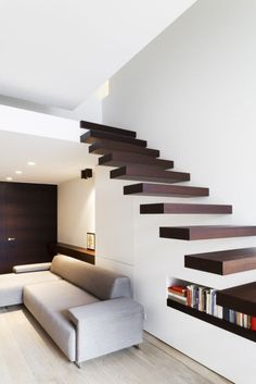 Very minimal staircase design with a small book storage beneath it.