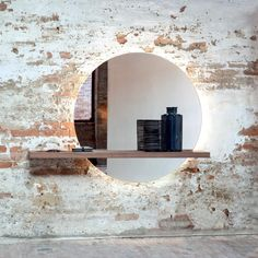 A simple round mirror is lit from behind, emitting a radiant light like the sun setting. http://www.yliving.com/blog/5-favorite-multifunctional-modern-mirrors/