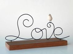 Escultura em arame com passarinho de cerâmica em base de madeira R$ 45,00