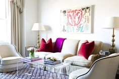 Tour a Cheerful and Elegant Family Home in NYC // red velvet throw pillows, nailhead occasional chair, diamond print rug, lucite coffee table