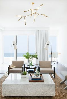 Minimalist modern beach house design. White walls and curtains, jute rug, square marble coffee table.