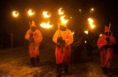 Hooded torch bearers lead the winter procession through the snow at the Imbolc pagan festival. Marsden, Huddersfield, in northern England.