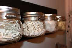 DIY mason jar bathroom organizer. Piece of wood, metal straps, small mason jars. Mount to wall. Fill jars with flossers, cotton swabs, cotton balls, etc. Perfect for a modern or industrial type decor.