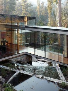 Linda casa nas montanhas com corredores e salas de vidro.