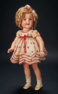 "Shirley Temple's own doll in, ""Stand Up and Cheer"" Costume by Ideal, circa 1934. 27"" All composition, hazel sleep & flirting eyes, human hair lashes open mouth, row of teeth -  mohair blonde wig in original ringlet-curled coiffure. The doll is wearing the red polka dot dress from Shirley's performance in the 1934 firm ""Stand Up and Cheer"", including dress with red sash and trim, panties/slip combination, socks and silver buckle shoes- dress having the woven NRA (National Recovery Act) label  Z"