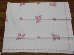 A vintage pure linen tablecloth with hand embroidered pink flowers and hand sewn edging.  This table cover measures fifty seven and a half inches wide  offered by rubylane shop Saltymaggie's Treasures