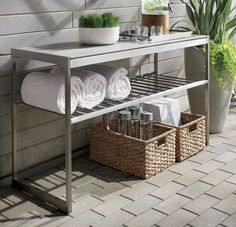 """Our urban style Dune collection is truly a modern """"indoor room"""" that lives outdoors. Backing a sofa or serving as a sleek bar, the console table offers a contemporary mix of materials, topping the stainless steel frame with tempered glass that's painted taupe on the underside for a modern, luminous look."""