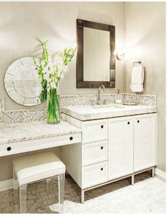 White bathroom cabinets with light gray walls. Hollywood Glam prevails in this master bathroom where a round mirror from Buckingham Interiors + Design hangs above the built-in vanity table and acrylic barstool. Corner Bathroom Vanity, Bathroom Table, Bathroom With Makeup Vanity, Bathroom Closet, Bathroom Vanity Lighting, Small Bathroom, Master Bathroom, Bathroom Vanities, Vanity Mirrors