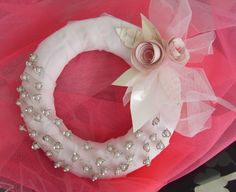 Soporte corona blanco para alfileres. En este caso, este soporte en forma de corona, aunque moderno, sigue el estilo elegante y tradicional de boda. Con adornos de flores y hojas en papel.
