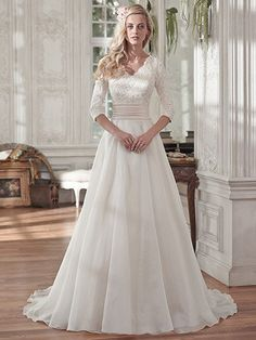 Maggie Sottero - BRENTLEIGH, Demure and sophisticated, this elegant sleeved wedding dress offers a gorgeous lace bodice, pleated Romance satin belt at the waist, and soft Vicenza organza skirt. Three-quarter sleeves lend a demure look to this A-line wedding dress. Finished with V-neckline and covered buttons over zipper and inner elastic closure.