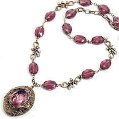 Sweet Romance Pink Amethyst Victorian Bohemia Locket Necklace Show someone you love just how important her love and friendship is to you when you give her a Sweet Romance locket with deep meaning. Made of delicate brass repousee elements with burnished bronze metal finish that struck from antique dies form an ornate setting atop an oval locket that measures 2 inches long. The etched glass Bohemian intaglio is hand made in the same process of the last 200 years pressing molten glass acid…