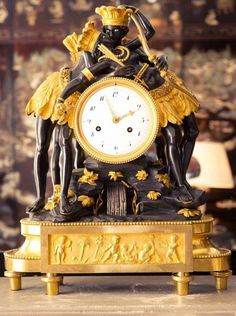 An intricate gilded clock sits atop a mantle in Coco Chanel's home