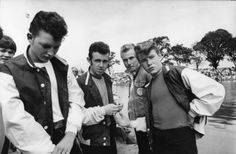 Clothing items usually worn by greasers included white or black t-shirts, denim jackets, leather jackets, Levi jeans with rolled up cuffs, motorcycle boots, army boots, Converse, and bandanas.     Typical hairstyles included the pompadour, Duck's tail, and more combed back Folsom style. Hair was held in place with hair wax or pomade.