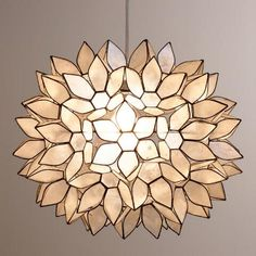 Handcrafted by skilled artisans in the Philippines, our Large Capiz Lotus Hanging Pendant Lantern features white capiz seashells formed into a gorgeous flower ball. The hand-collected natural capiz shells glow with a warm radiance when illuminated, creating a soothing ambiance. Hang this gorgeous ball pendant with one of our Cord Swag or Ceiling Hardware Kits to imbue your home décor with elegance.
