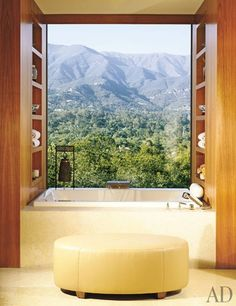 """Envisioning a house where """"every window would be a picture,"""" Robert and Alexandra Norse commissioned architect Jack Lionel Warner and designer Barbara Barry to build their home in Montecito, California. In the master bath, the tub is installed between a pair of stately walnut shelving units, which display ceramics and provide easy access to stacked towels while framing the extraordinary mountain views. (May 2005)"""