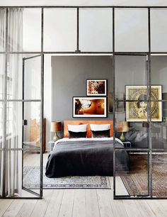 Elle Decoration UK | Bedroom design ideas, love the glass grid panel separating bedroom, and pops of orange in the midst of the grey tones. #home #interior