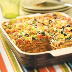 Mexican Lasagna - layers of beef with taco seasoning, refried beans, and plenty of cheese stacked between either lasagna noodles or tortillas and topped with sour cream, olives, onions, and tomatoes if desired.