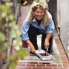 """Give your concrete walkway a face-lift. Sweep the surface, then prime it with a concrete resurfacer, like Rust-Oleum's Epoxy Shield. Let dry; then, starting in one corner, use a 4-inch roller to create a """"brick"""" with a terra-cotta-hued concrete paint. Fill the space in between with a running bond pattern of 8-inch bricks. Don't worry about keeping them exactly the same size or the lines pin-straight. Via ThisOldHouse.com"""
