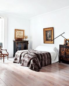 The oversize fur comforter makes this white-wall, antique-filled room impossibly cozy