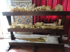 Mobiliário com três prateleiras, adequando-se para recebimento de ex-votos em parafina. Tipologias variadas (cabeças, pés, pernas, órgãos humanos, braços), e as tradicionais velas.