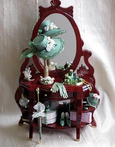 Stylish Ornate Ladies Dresser with Accessories.   The dresser has a rich mahogany coloured finish. It is filled with essential ladies items in shades of green. Everything is fixed into place. Also included is also a pretty Umbrella which is loose to display as you wish.