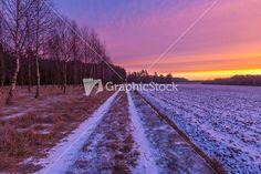 Beautiful winter sunrise or sunset landscape. Sun over agricultural field.