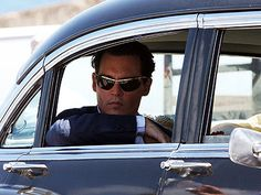 The actor is dapper, down to his gold-edged sunglasses, as he sneaks a peek out of his vintage car window while filming The Rum Diary in Puerto Rico.