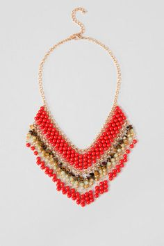 "Adorn your neckline in natural opulence with the Rena Statement Necklace. A combination of red glass beads, natural stones and faceted jade beads create the abundance of fringe that make up this collar necklace. Add the Rena Statement Necklace to a crochet top and printed leggings for a transitional look. <br />  <br />  - 17"" length<br />  - 3"" extension<br />  - Lead and nickel free<br />  - Imported"