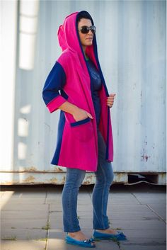"Straight hooded coat in contrasting blue and raspberry colors featuring a wide hood which switches to a ""scarfy"" collar, an open front or may be belted waist, 3/4 sleeves, one patch pocket and a mid-length."