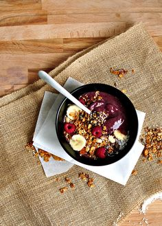 This acai bowl has a thick acai base, topped with crunchy granola filled with nuts, fresh fruit and coconut. It's a healthy, infinitely adaptable breakfast.