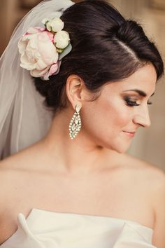 A stunning updo perfectly shows of this bride's sparkling earrings and flower hair piece. Flowers by Stems of Dallas. Gown from The Bridal Salon at Neiman Marcus.  Photo by Shaun Menary. #wedding #updo #flowers #veil