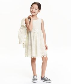 Sleeveless lace dress with a decorative grosgrain bow at front. Small opening at back of neck with button, seam at waist, and flared skirt with scalloped hem. Jersey lining.