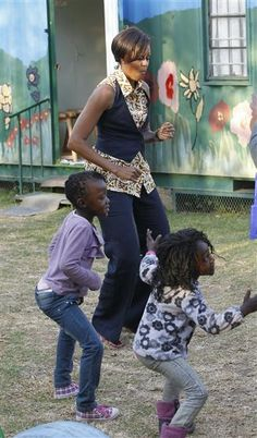 Michelle dances with children as she visits the Emthonjeni Community Center in Zandspruit Township, Johannesburg, South Africa