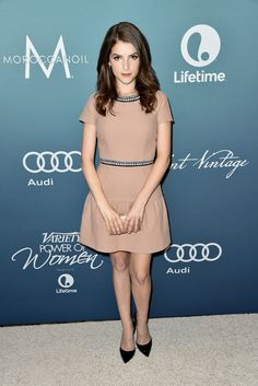 Anna Kendrick wears a blush pink dress with black and white piping with pointed-toe pumps