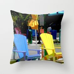This design is an original photograph of Adirondack style chairs in bright tropical colors, arranged outdoors in a town by the sea.