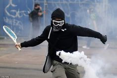 A protestor uses a tennis racket to return a tear gas canister during a demonstration to protest the government's proposed labour law reforms in Nantes, France, on June 2
