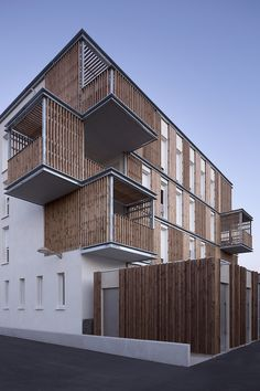 designed by TLA architectes and composed of 15 social housing complexes, a tax center and a police station, the exterior is characterized by its rhythmic timber cladding.