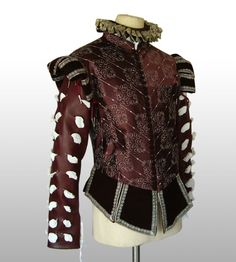 Chevroned dark brown silk fabric with silver embroidery for the doublet matched with a dark brown silk velvet for the epaulets and tabs. Accessorized with a ruff made of vintage double-faced satin ribbon and metallic silver lace. Matching Slops with same fabrication.