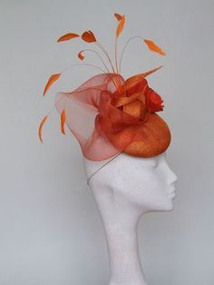 A very stylish orange sinamay button fascinator with a large hand crafted silk rose, feathers and crinoline. Perfect when you dont feel like wearing a large hat. Gorgeous statement fascinator for weddings and race days. Secured by hat elastic In stock for immediate despatch Please get in touch for shipping costs to destinations not listed.