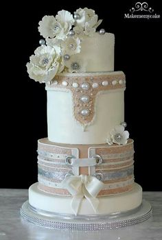 Luxury Wedding Cake in champagne and vanilla buttercream and edible silver spheres, corset tie. Enjoy RUSHWORLD boards, WEDDING CAKES WE DO, WEDDING GOWN HOUND and UNPREDICTABLE WOMEN HAUTE COUTURE. Follow RUSHWORLD! We're on the hunt for everything you'll love! #WeddingCakesWeDo #LuxuryWeddingCake #WeddingCake