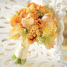 Bridal bouquet of orange princess tulips, peach Parrot tulips, cyrthanthus and lady's mantle.