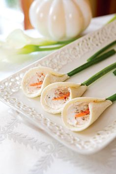 Calla Lily Tea Sandwiches (4 dozen) - 1 (5.2-oz) package garlic and herbs cheese, softened; 1 (3-oz) package cream cheese, softened; 1/4 cup finely chopped toasted walnuts; 1/8 tsp ground red pepper; 1/8 tsp ground black pepper; 48 slices white bread;  Paprika; 2 carrots, peeled; Garnish: green onion.