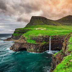 Se é verdade que as melhores dicas de viagem mostram lugares longínquos e para poucos a de hoje vai quebrar algum recorde. A vila que você vê na foto no meio de um gramado e no alto de uma falésia enorme  que ainda por cima é cenário para uma cascata magnífica  chama-se Gasádulur e fica nas Ilhas Faroe uma possessão dinamarquesa bem no norte do planeta. A vila é acessível através de um túnel rodoviário que a liga a estrada principal da ilha de Vágar (uma das Faroe). Mas leve sua própria…